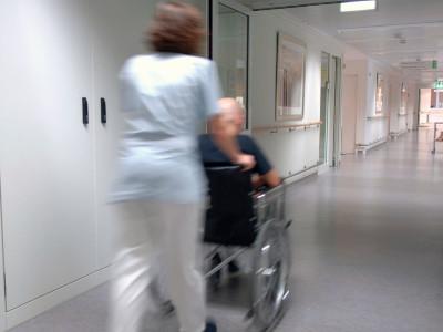 Pflegekraft schiebt Rollstuhl im Krankenhaus